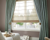 Sheer Hunter Douglas Design Studio Roman shades complemented by side panels give a bit of privacy to this window.